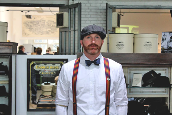 a dapper man wearing goorin bros flatcap, bowtie and suspenders